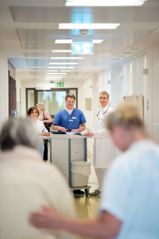 Healthcare photography: Medical consultation in a hospital. Two doctors and a nurse at the case discussion in the hallway. One patient in the foreground is directed by a nurse.