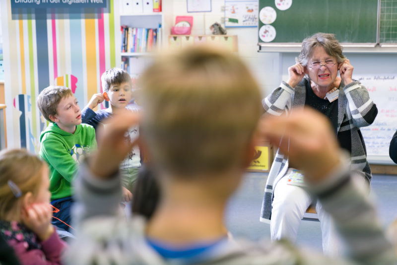 Editorial photography, subject learning and education: During a reading lesson at a primary school, the teacher encourages the children to pull their ears.