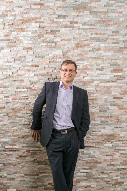 Managerportrait: Vorstandsvorsitzender im Portrait vor einer interessant strukturierten Backsteinmauer. Er lacht in die Kamera. Das Bild ist mit mehreren Blitzgeräten mit Lichtformern ausgeleuchtet. Er trägt einen Anzug und ein lila Hemd ohne Krawatte.
