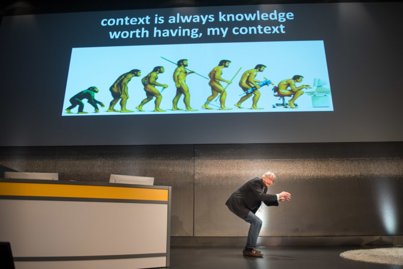 Editorial photography as event photography and fair photography: In a presentation to IT scientists, the speaker imitates a person on a computer. On the beamer picture you can see a drawing showing the development of humans from monkeys and their return to the bent monkey posture in front of the computer.