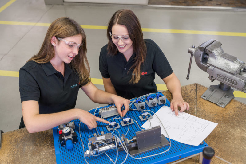 Editorial photography: Two female trainees work together on a hydraulic circuit.