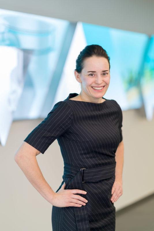 Managerportrait: Eine weibliche Führungskraft im Kostüm. Sie wurde als Halbportrait fotografiert und steht vor einem blau leuchtenden Display im Showroom der Firma.