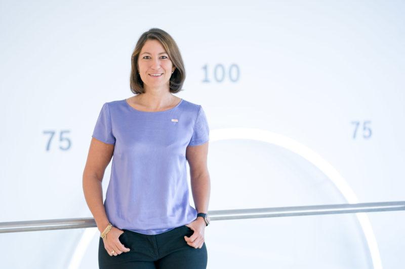 Managerportrait: Eine weibliche Führungskraft einer IT-Abteilung im Foyer Ihrer Firma. Sie steht lässig an einem Geländer. Im Hintergrund sieht man Zahlen auf der großen, hellen Wand.