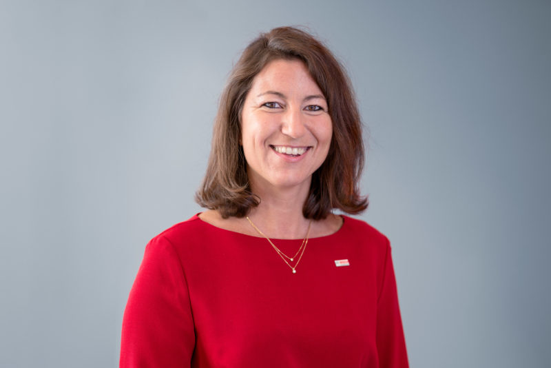 Managerportrait: A female manager in a red sweater against a grey background. She smiles into the camera and wears a small badge of her company and jewellery.