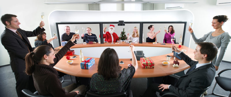 Fotomontage mit Photoshop: Eine Collage für die Weihnachtspost: Mitarbeiter sitzen im Videokonferenzraum und stoßen mit ihren Kollegen auf den Bildschirmen auf das neue Jahr an.