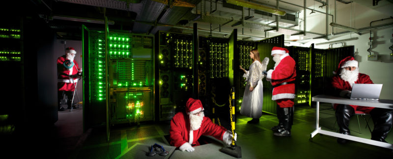 Photomontage with Photoshop: Christmas photo for an IT company: Red Santa Clauses and an angel work in the green-lit server room.