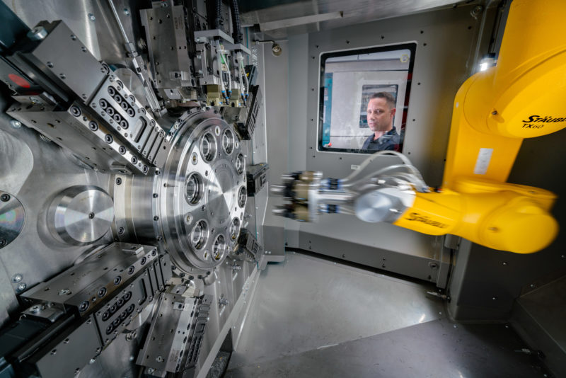 Industrial photography: A yellow robot arm works in a machine tool on a large metal part. An employee looks through the glass pane into the interior of the machine.