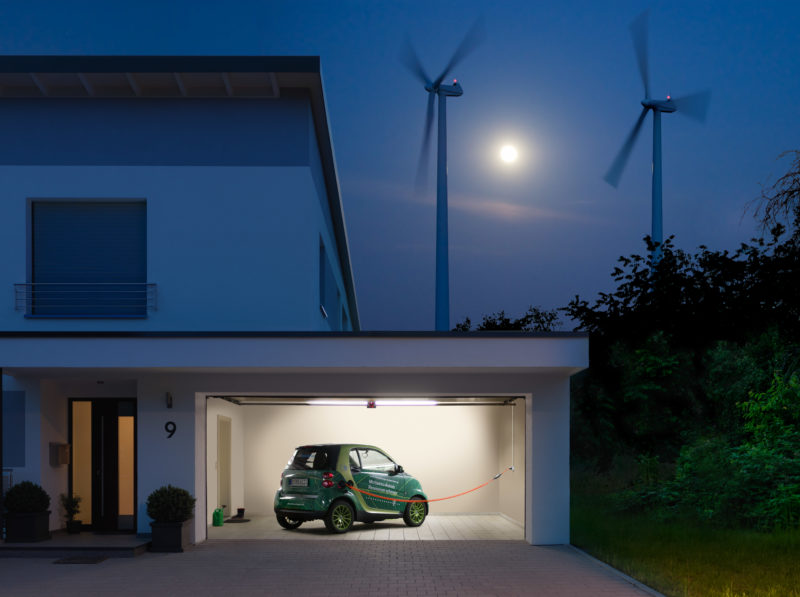 Technology photography:  Electric vehicle that is charged by wind power during the night in the garage.