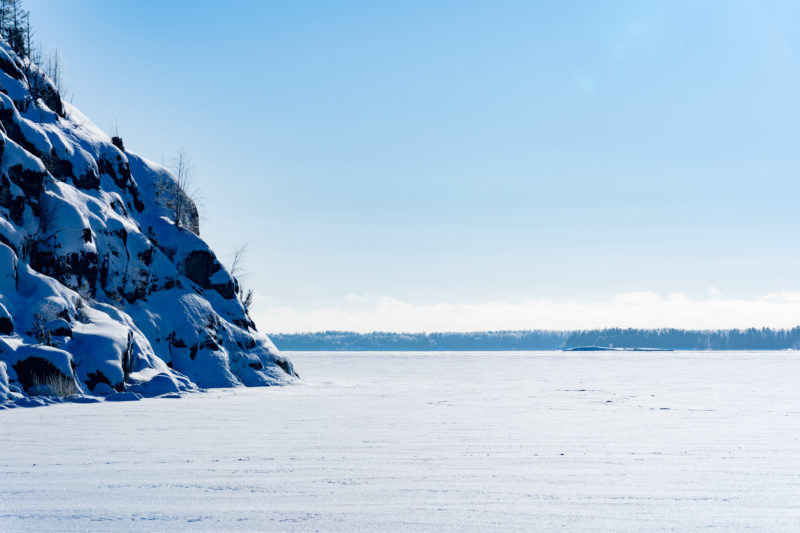 Landscape photography: Winter in Finland: View of an ice-covered Baltic Sea bay, on the left typical rocks at the Baltic coast of Finland.