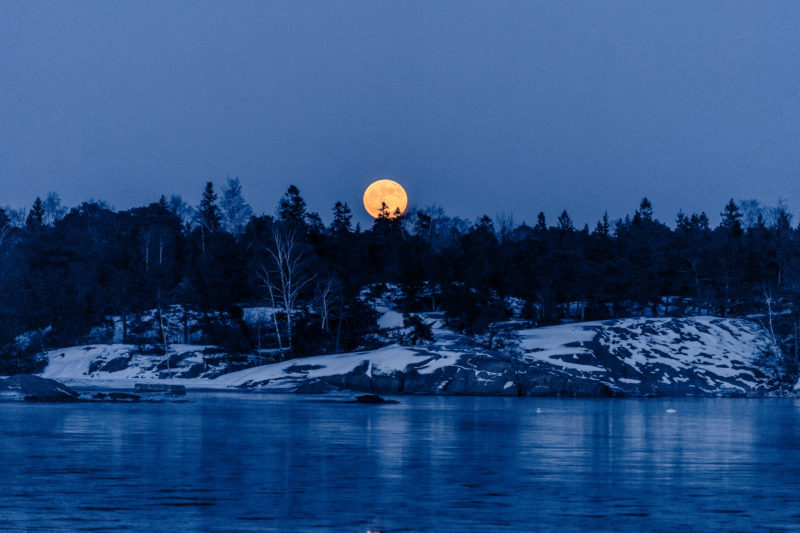 Landscape photography: Winter in Finland: The rising red moon over the typical snow-covered rocks of the Baltic Sea coast.