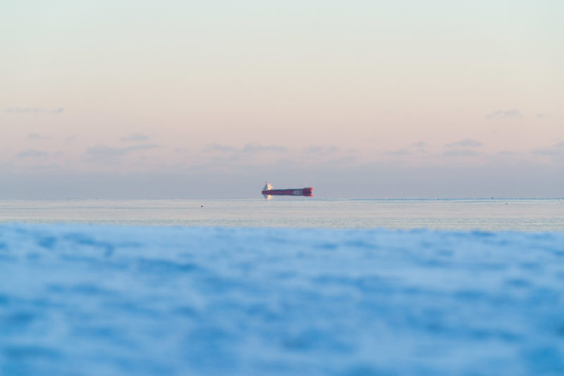 Landscape photography: Winter in Finland: A ship sails on the horizon in the waters of the ice-cold winter Baltic Sea. Through the air movements and reflections it looks as if it is floating in the air.