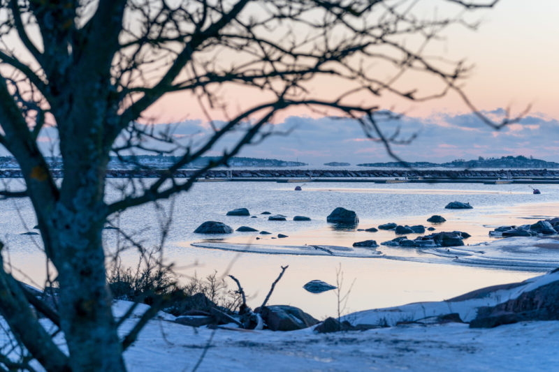 Landscape photography: Winter in Finland: Small islands with polished rocks with snow and ice in reddish diffuse sunlight give a typical winter view of the Baltic Sea coast.
