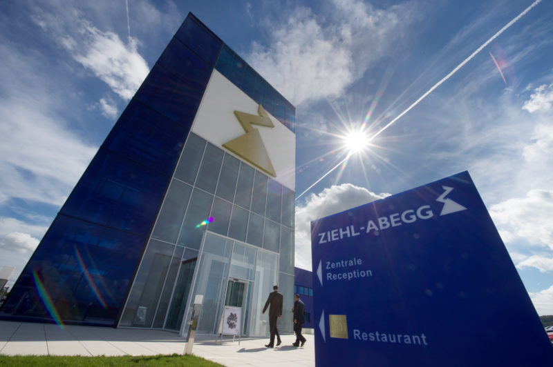 Architectural photography: Modern Ziehl-Abegg company headquarters from the outside. In the foreground you can see the blue company sign against the slightly cloudy blue sky with the shining sun, pointing to the entrance of the main building on the left side.