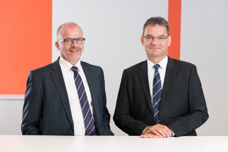 Managerportrait: Zwei Führungskräfte an einem Stehtisch. Im Hintergrund sind senkrecht angebrachte orangerote Wandelemente.