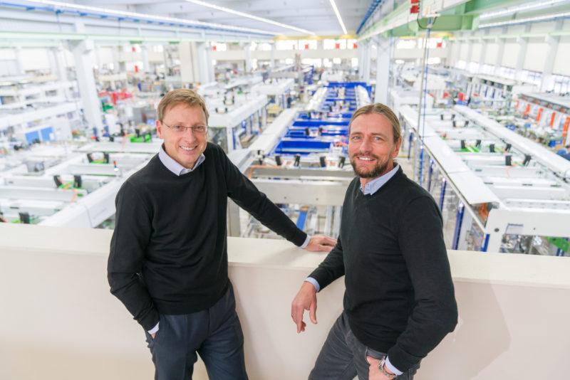Managerportrait: Zwei Geschäftsführer stehen locker in einer der Werkshallen ihrer Firma. Sie schauen lachend in die Kamera. Das Foto ist mit einem indirekt eingesetzten Blitzgerät von einer Leiter aus aufgenommen.
