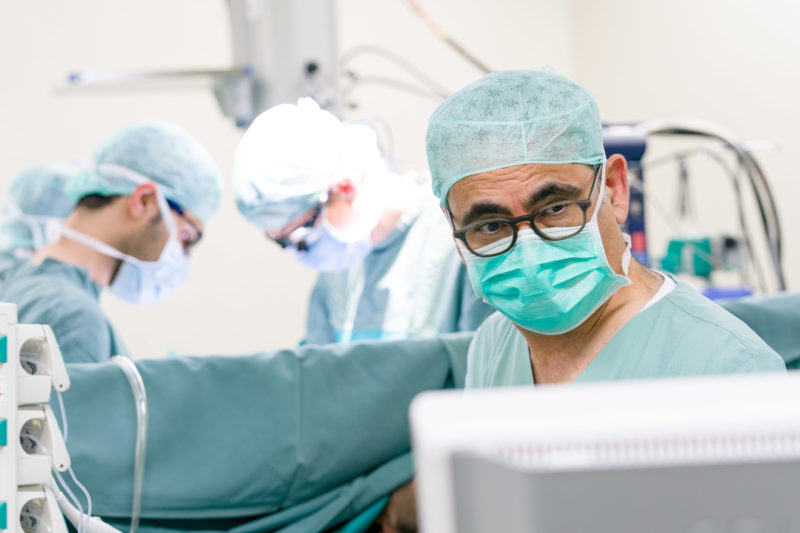 Healthcare photography:  An experienced heart surgeon before an operation begins. He checks the existing images and data on a display next to the operating table.