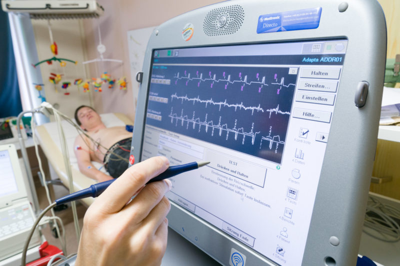 Healthcare photography: An ECG is written in the outpatient department of pediatric cardiology at Homburg University Hospital (Saar) to check and adjust the pacemaker of an adolescent. In the background you can see the young patient with the ECG cables connected to the chest.