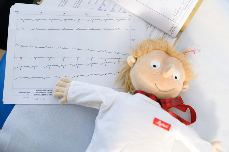 Healthcare photography:  In the pediatric cardiology department of the University Hospital Homburg (Saar) a toy doll is lying on the printouts of an ECG.
