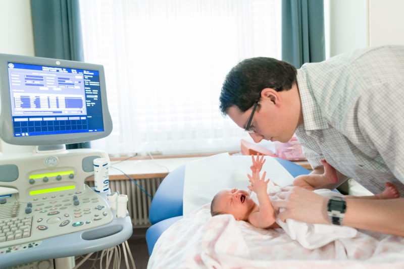 Healthcare photography:  In the pediatric cardiology department, a father takes care of his crying baby.